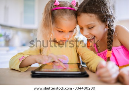 Two beautiful little sisters sit at a table and play on a Tablet PC. - stock photo