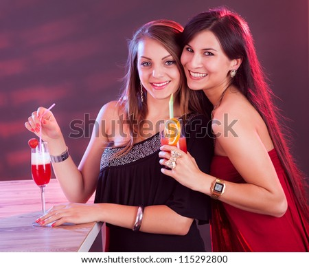 Two beautiful long haired female friends partying at a bar counter with cocktails in their hands under colorful lighting in a nightclub - stock photo