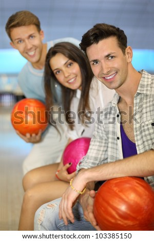 Two beautiful men and woman hold balls in bowling club; shallow depth of field; focus on right man - stock photo