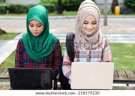 two beautiful muslim girl study together with laptop at the universiy park - stock photo