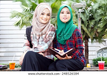 Two beautiful muslim girl study together with notebook at the park - stock photo