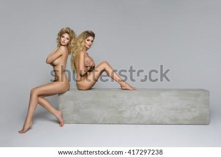 Two beautiful naked women on concrete block  - stock photo