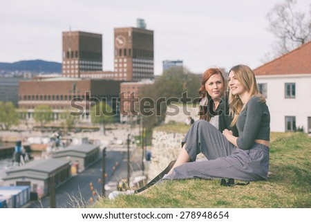 Two beautiful nordic girls enjoying their spare time in Oslo, talking and laughing, with harbour and town hall on background. Lifestyle and friendship concepts. - stock photo