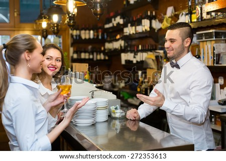 Two beautiful russian girls flirting with handsome barman