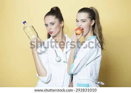 Two beautiful sensual girls doctor and nurse in white medical uniform with stethoscope eating fresh red apple and holding bottle of mineral water standing on yellow background, horizontal picture - stock photo