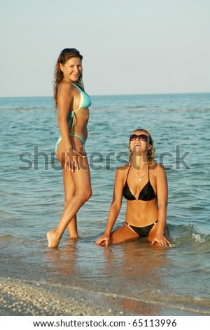 Two beautiful sexual girls pose on beach in swimsuit - stock photo