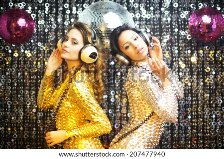 two beautiful sexy disco women in gold and silver catsuits dancing in a club setting. Useful for fashion, beauty, music and events - stock photo