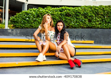 Two beautiful sexy fashion cool pretty girls, blond and brunette, sitting on the steps in front of the shopping center. Dressed in colorful T-shirts with his lips and pineapple, shorts, sunglasses. - stock photo