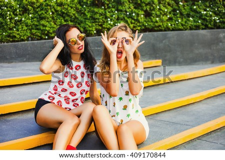 Two beautiful sexy fashion cool tanned happy pretty cheeky hipster girls, blond and brunette, sitting on the steps in front of the shopping center. T-shirts with lips and pineapple, shorts, sunglasses - stock photo