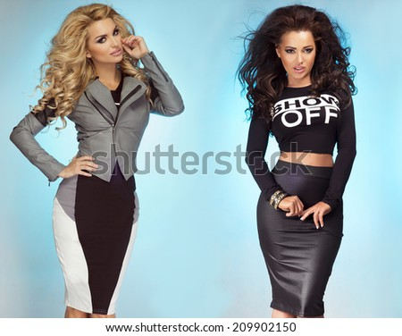 Two beautiful sexy sisters posing over blue background. Girls with long curly hair and perfect makeup. - stock photo