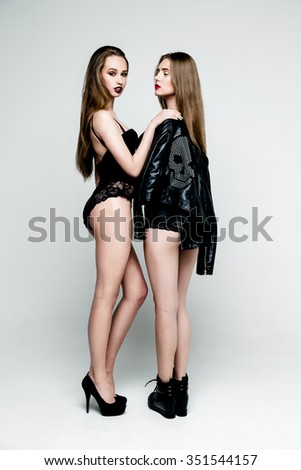 Two beautiful sexy women in leather jacket and underwear on white background