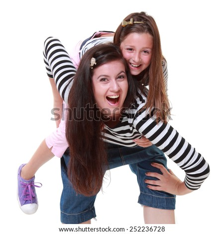 Two beautiful sisters dressed in an urban style of smiling and posing for the camera on a white background on Beauty and Fashion - stock photo