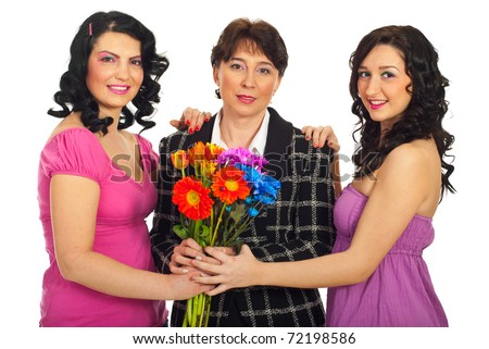 Two beautiful sisters giving flowers to their mother and standing together in a hug isolated on white background