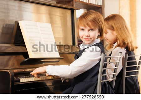 Two beautiful small girls playing piano indoors - stock photo