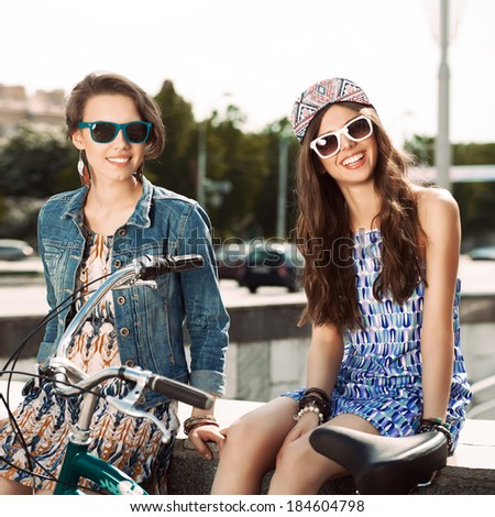 two beautiful smiling girls in sunglasses with a bike in the city - stock photo