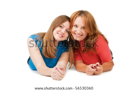 Two beautiful smiling girls lie on a floor, isolated on white