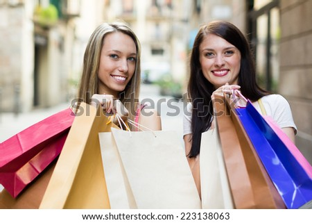Two beautiful smiling girls with shopping bags in the street