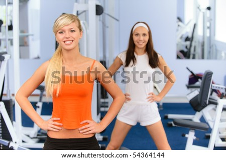 Two beautiful smiling sportswomen do exercises in big sports hall. - stock photo