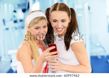 Two beautiful smiling sportswomen read sms on phone in big sports hall.