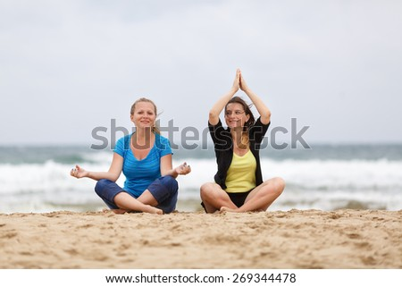 Two beautiful smiling young woman sitting in lotus pose on the sand on the beach and relax. Shallow depth of field. Focus on the models. - stock photo
