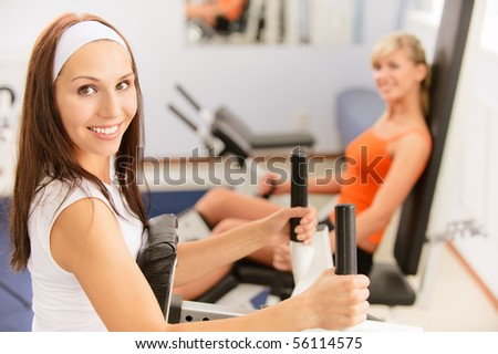 Two beautiful sportwomen make exercise on training apparatus