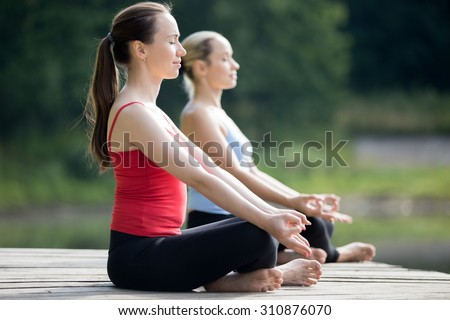 Two beautiful sporty fit young women sitting in Easy (Pleasant Posture), Sukhasana, meditating with closed eyes, breathing, working out outdoors in summer, wearing red and blue tank tops sportswear - stock photo