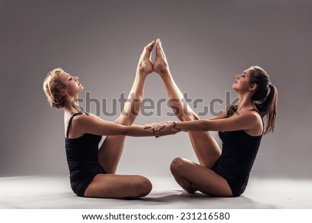 Two beautiful sporty women doing stretching exercise - stock photo
