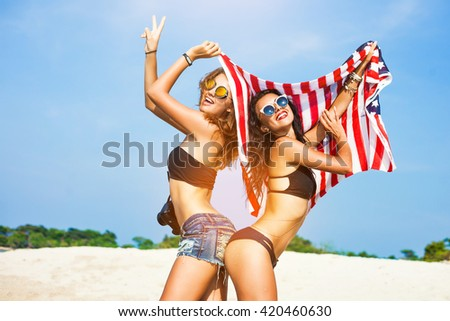 Two beautiful tanned fun hipster girls on the beach, blonde and brunette standing back to back and holding an American flag, old style, laugh, smile relax on a tropical island sexy bikini denim shorts - stock photo