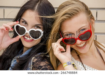 Two beautiful teenage girl wearing funny sun glasses - stock photo