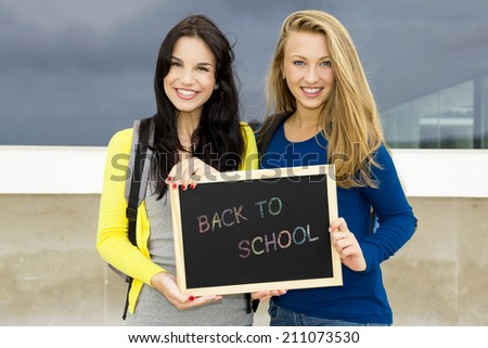 Two beautiful teenage students holding a chalkboard with the slogan Back to School - stock photo