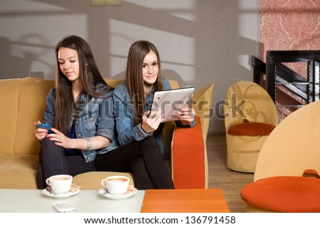 Two beautiful teens absorbed using their computer gadgets. - stock photo