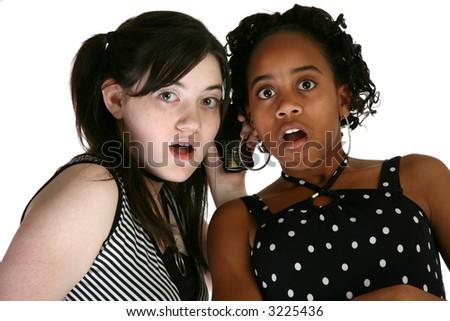 Two beautiful thirteen year old girls sharing cellphone. - stock photo