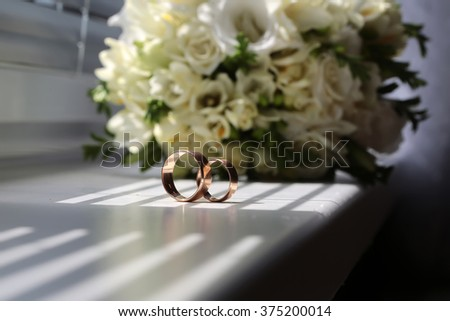 Two beautiful wedding golden rings tradition jewelry symbol of love and unity on wedding ceremony in background of splendid bridal bunch of creamy white roses and tulips closeup indoor, horizontal - stock photo
