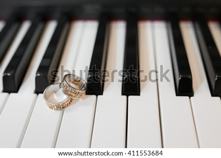 Two beautiful wedding rings on piano keyboard in close-up - stock photo