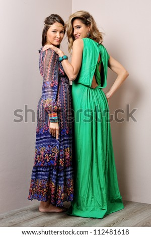Two beautiful woman in long dresses. - stock photo