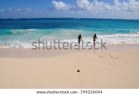 Two beautiful woman play in a turquoise beach in Barbados - stock photo