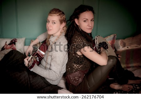 two beautiful woman with guitar - stock photo