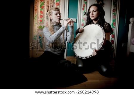 Two beautiful woman with  tambourine - stock photo