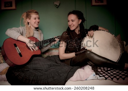 two beautiful woman with  tambourine and guitar - stock photo