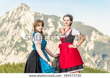 Two beautiful woman with traditional austrian clothes in the alps