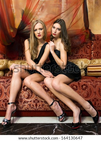 Two beautiful women are sitting on the sofa in a oriental interior