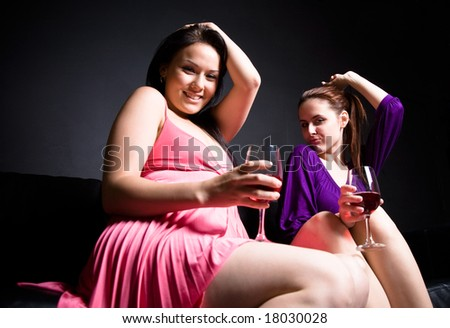 Two beautiful women dancing and drinking wine during a party - stock photo