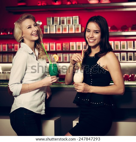 Two beautiful women drinking cocktail in a night club
