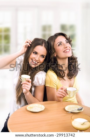 Two beautiful women drinking coffee and chatting - stock photo