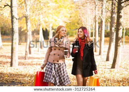 Two beautiful women having a relaxing conversation with coffee after shopping walking in the autumn park.