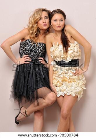 Two beautiful women in fancy dresses. Studio portrait. - stock photo