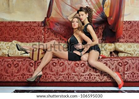 Two beautiful women in luxury oriental styled interior. - stock photo