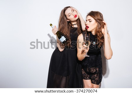 Two beautiful women in night dress  posing with champagne isolated on a white background  - stock photo
