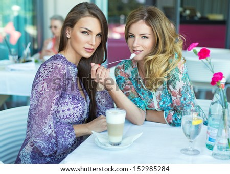 Two beautiful women in restaurant drinking coffee and water - stock photo