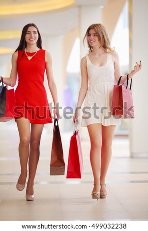 Two beautiful women in short dresses go with bags in shopping center